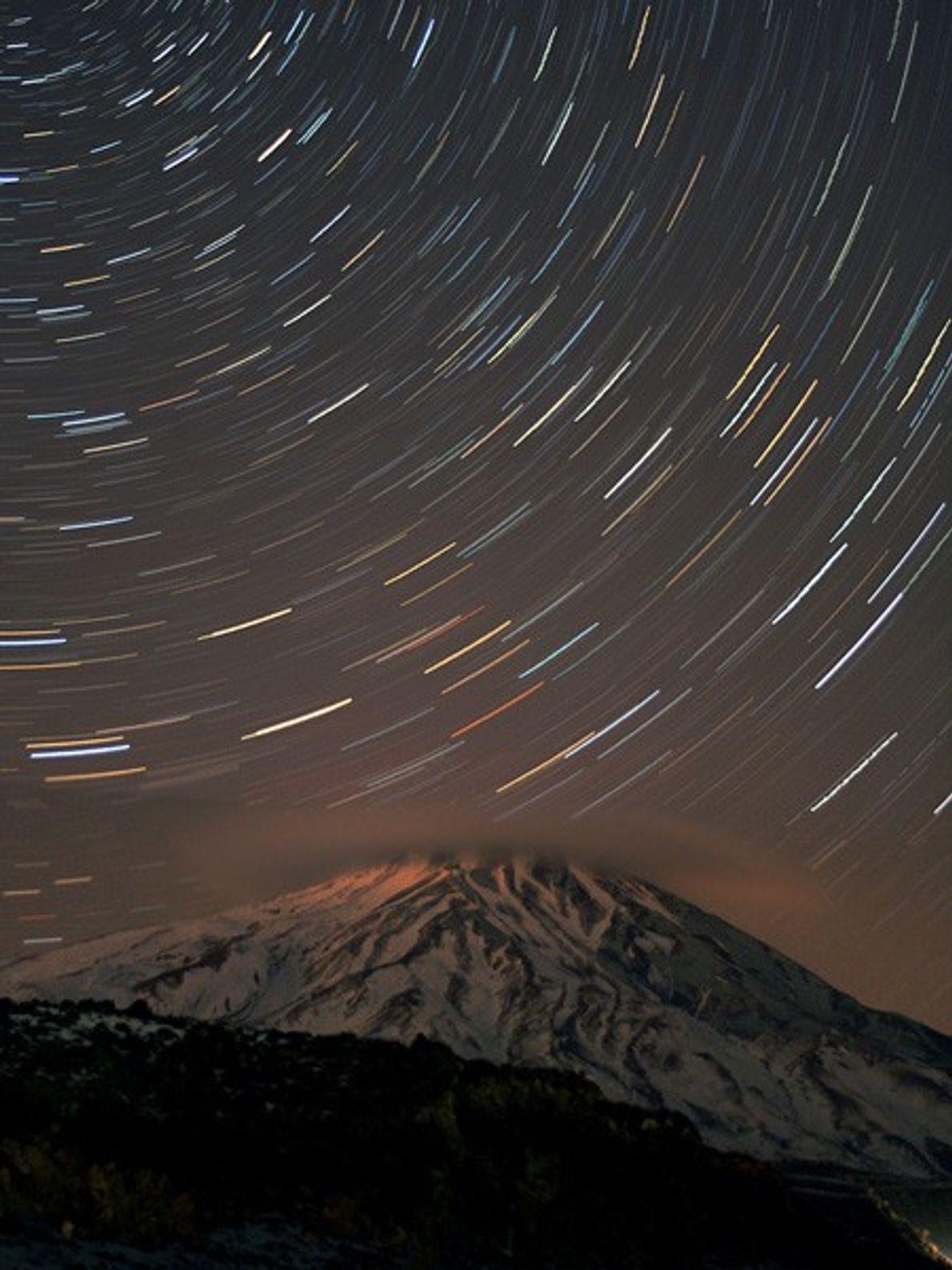 Des étoiles tournoient dans le ciel nocturne au-dessus du Mont Damavand, en Iran. La montagne, qui ...