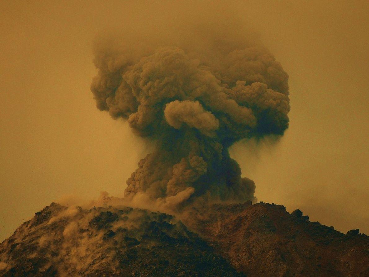 Le volcan Arenal au Costa Rica éclate brusquement en février 2010, teintant le ciel d'un jaune-brun ...