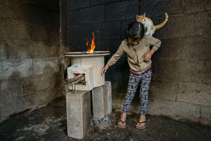 Dans une pièce aux murs noircis par un vieux feu de cheminée, Tania López, âgée de ...