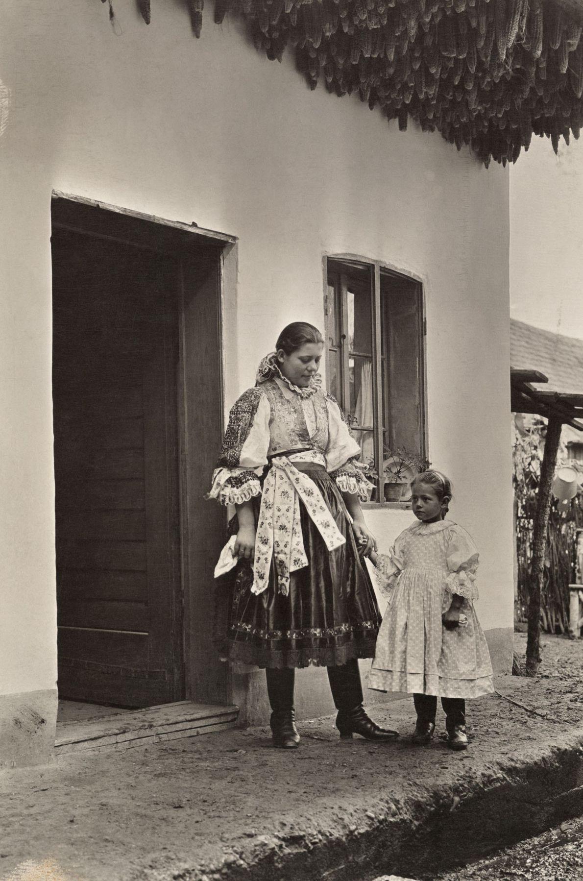 Une mère et un enfant se tiennent sous le maïs mis à sécher à l'entrée de ...