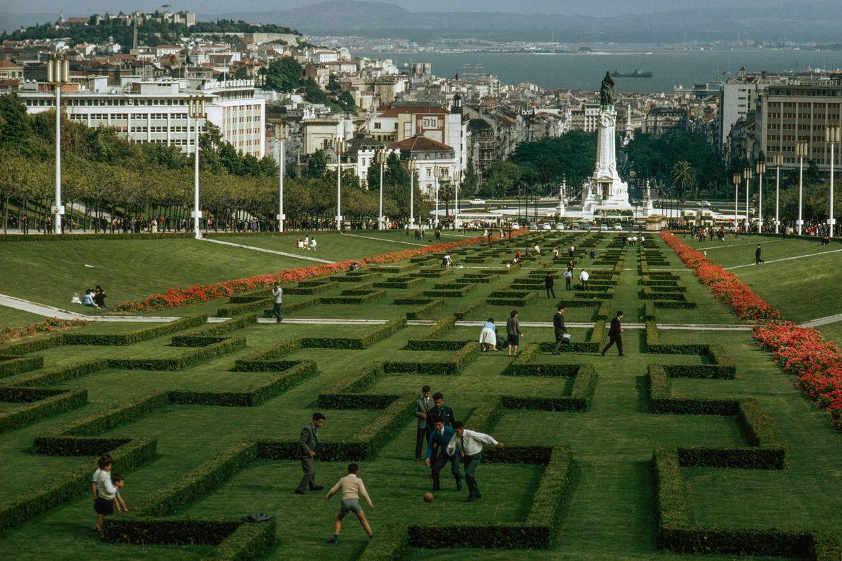 Alors que des gens se promènent dans un jardin sculpté de Lisbonne au Portugal, un groupe ...