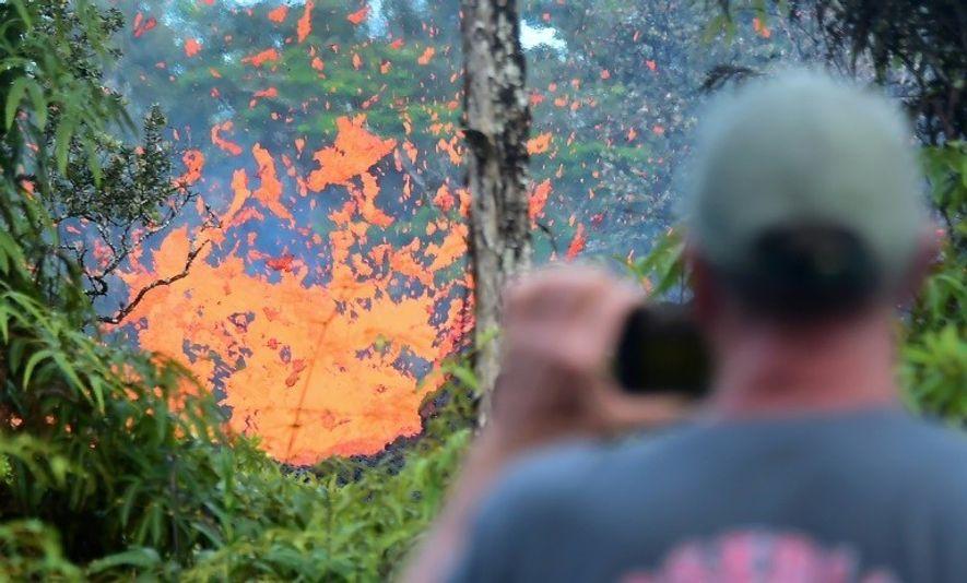 Un homme regarde la lave jaillir d'une fissure dans le quartier Leilani Estates, à Hawaï le ...