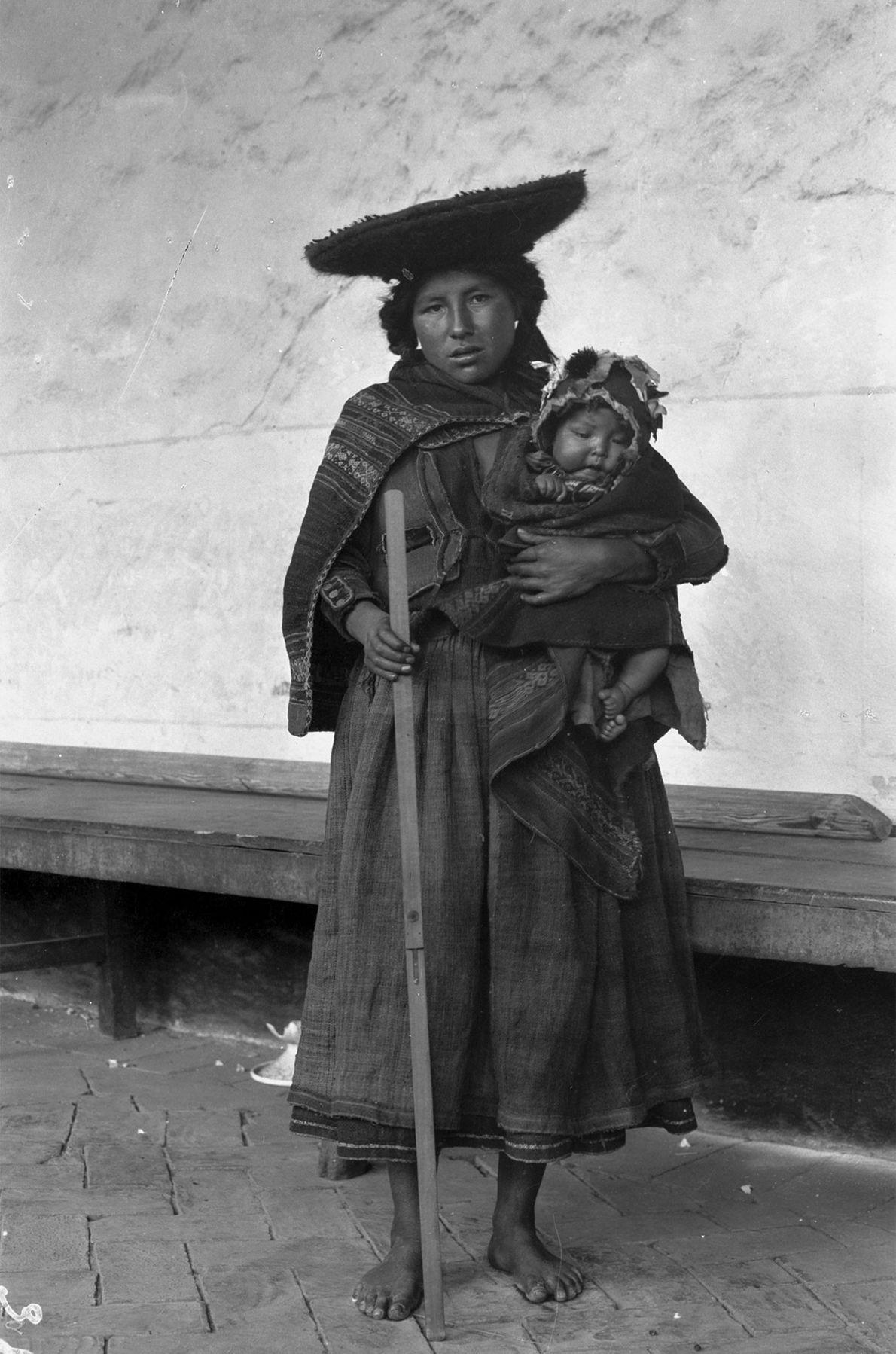 Une mère tient son bébé dans ses bras tout en posant pour une photo dans la ...