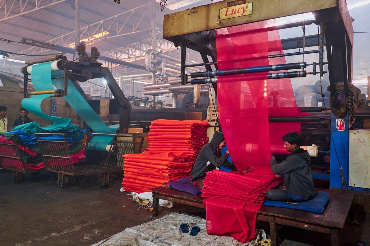 Les ouvriers d'une usine textile au Rajasthan retirent les tissus des métiers géants. Les tissus sont produits en ...