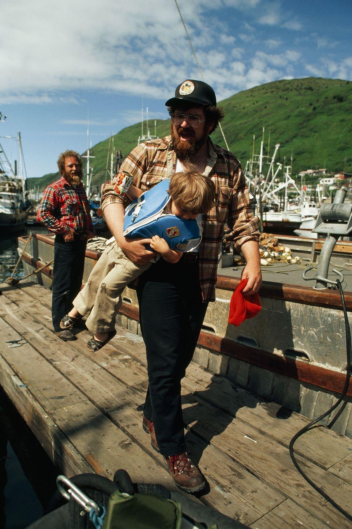 Un homme porte son fils alors qu'il marche sur une jetée de l'île Kodiak en Alaska ...