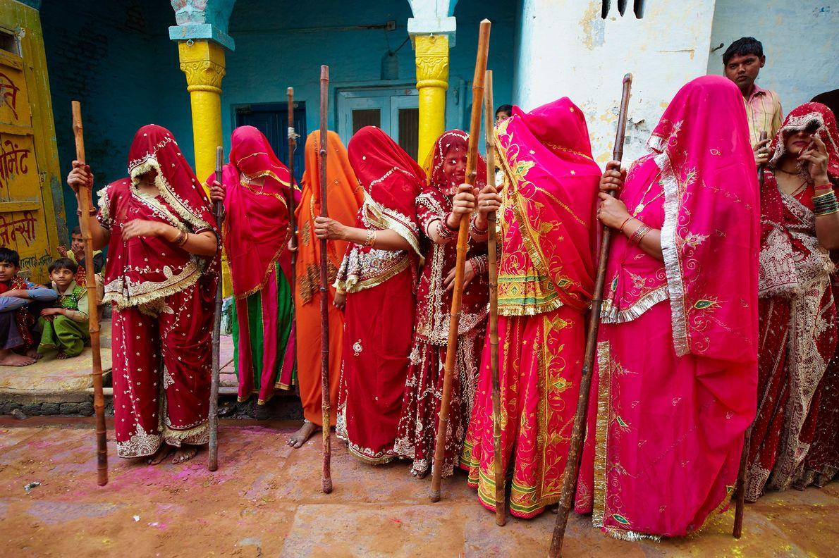 Pendant le festival Holi dans l'Uttar Pradesh, en Inde, les femmes portent des saris rouges traditionnels ...
