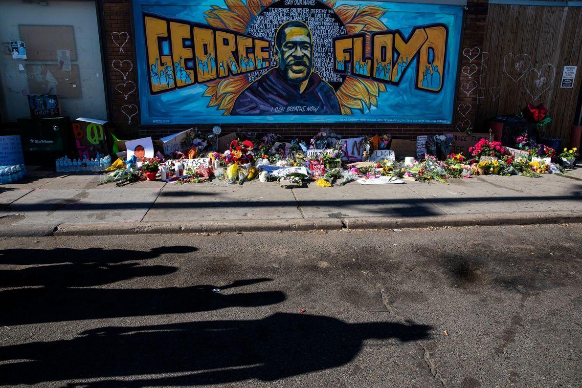 Une fresque représentant George Floyd surplombe les fleurs et les bougies laissées par les habitants du quartier, en ...
