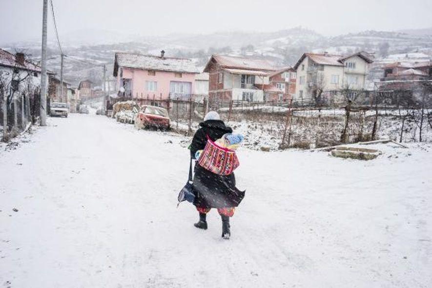 A Ribnovo, une femme pomak transporte son bébé dans la neige.