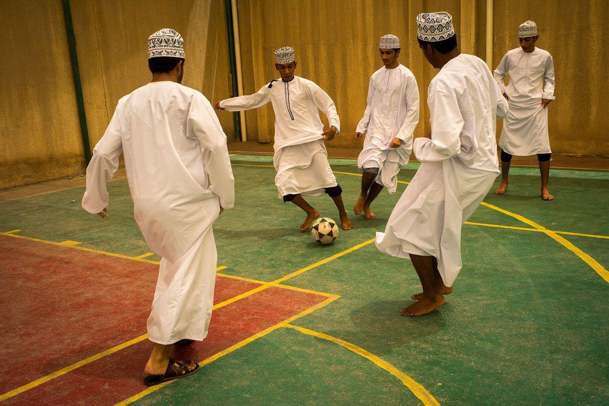 Vêtus d'une dishdasha traditionnelle, un groupe de jeunes hommes jouent au foot en salle à Al ...