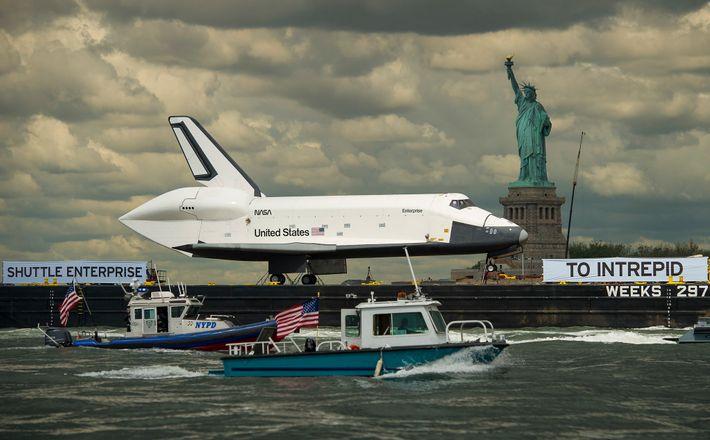 Attachée sur une barge, la navette spatiale Enterprise passe devant la Statue de la Liberté sur ...