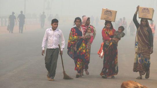 Des piétons dans une rue de New Delhi dans un brouillard polluant, le 9 novembre 2017 ...