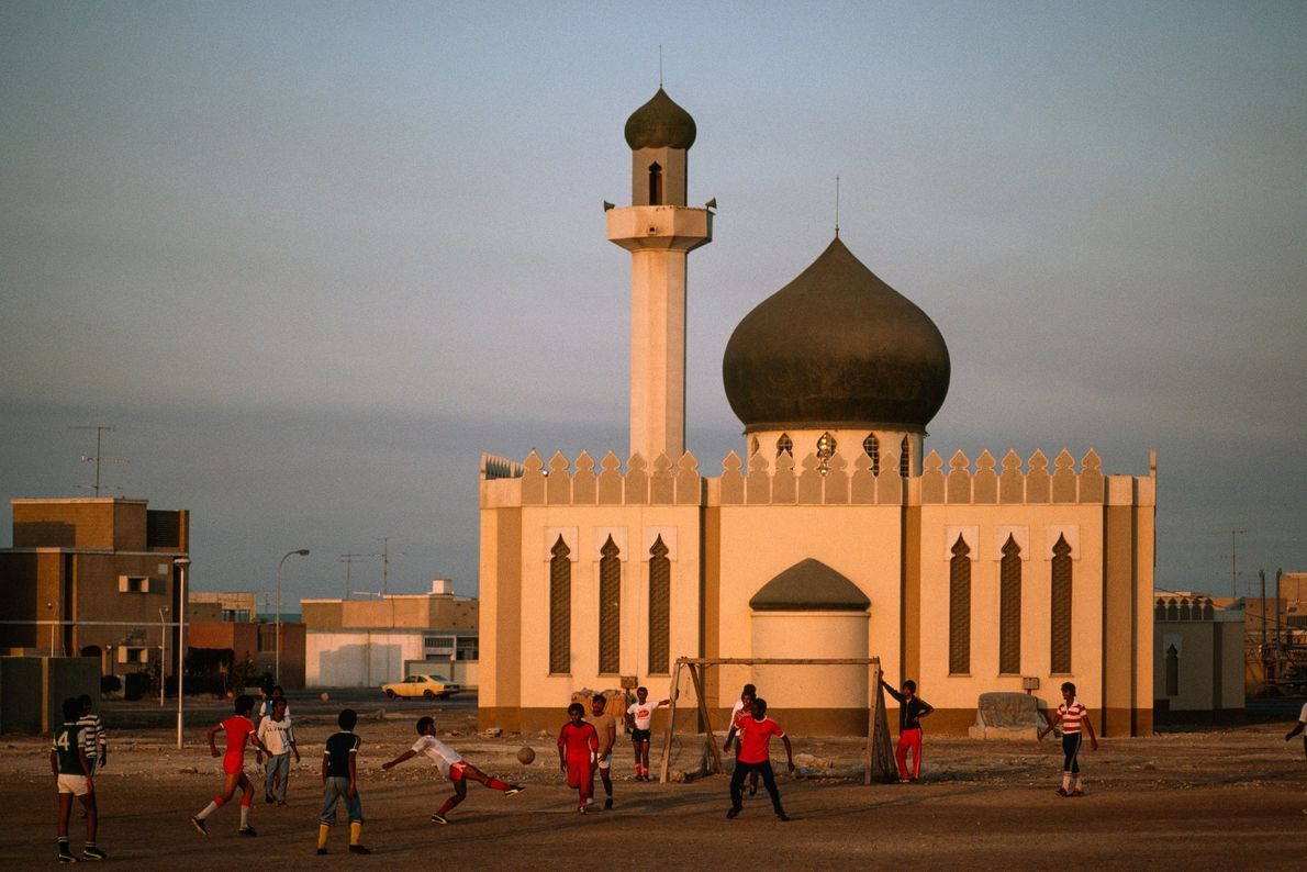 En 1979, à Bahrein, des garçons jouent au football devant la mosquée de Madinat 'Isa, fraîchement ...