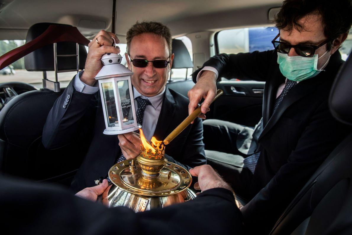 Christos Sofianopoulos, le Consul général grec de Jérusalem (à droite) enflamme une lanterne conçue pour le ...