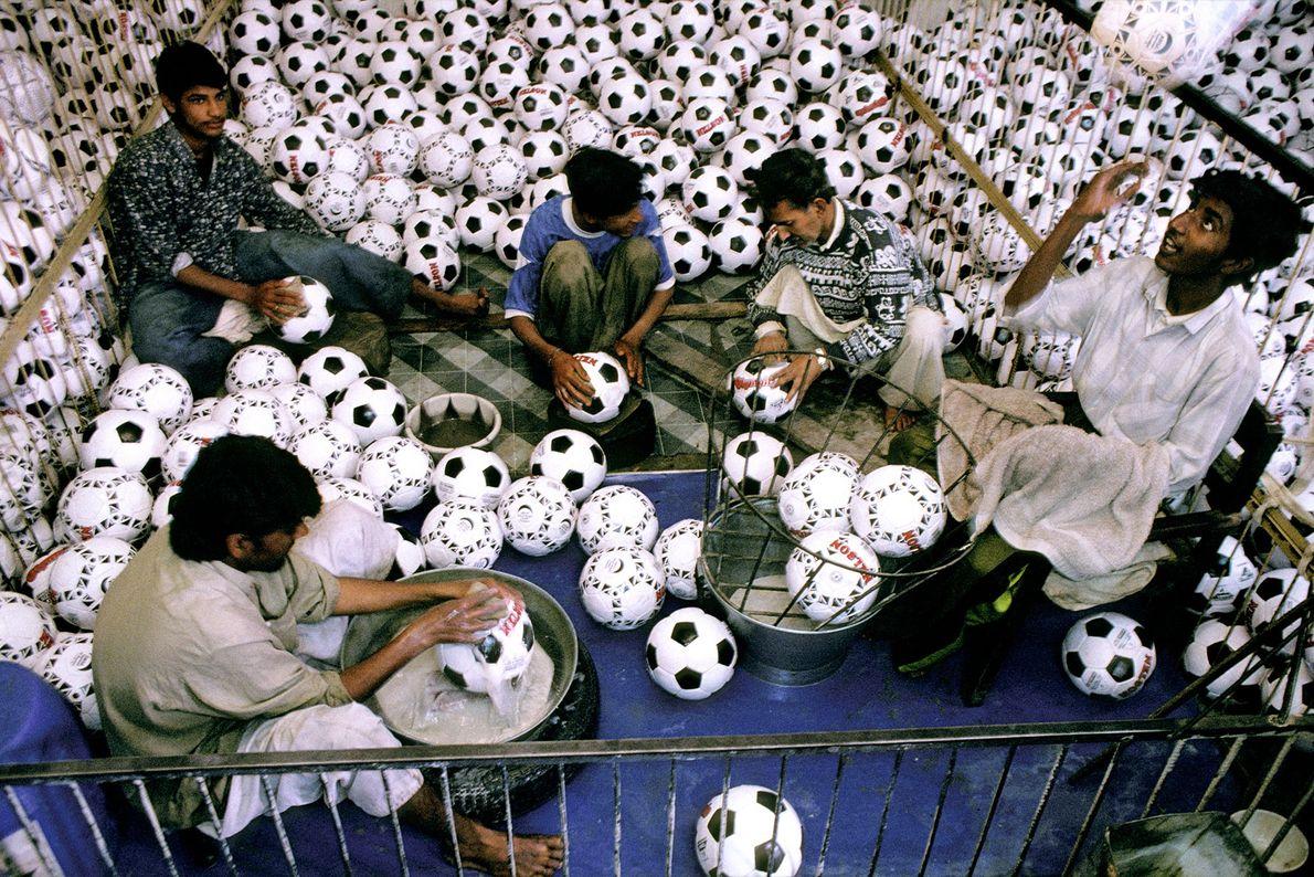 Sur ce cliché pris en 1998 au Pakistan, de jeunes travailleurs lavent des ballons de football ...