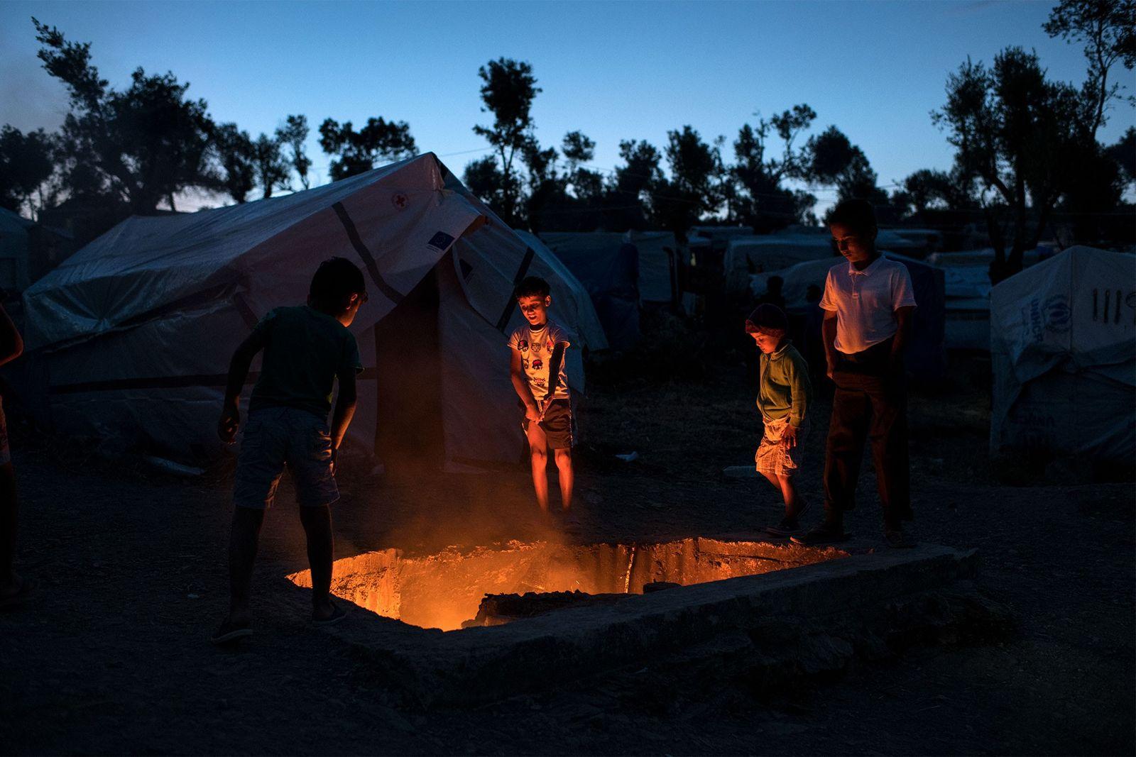 Des enfants réfugiés se tiennent autour d'une fosse où brûlent des déchets. Si le feu permet ...