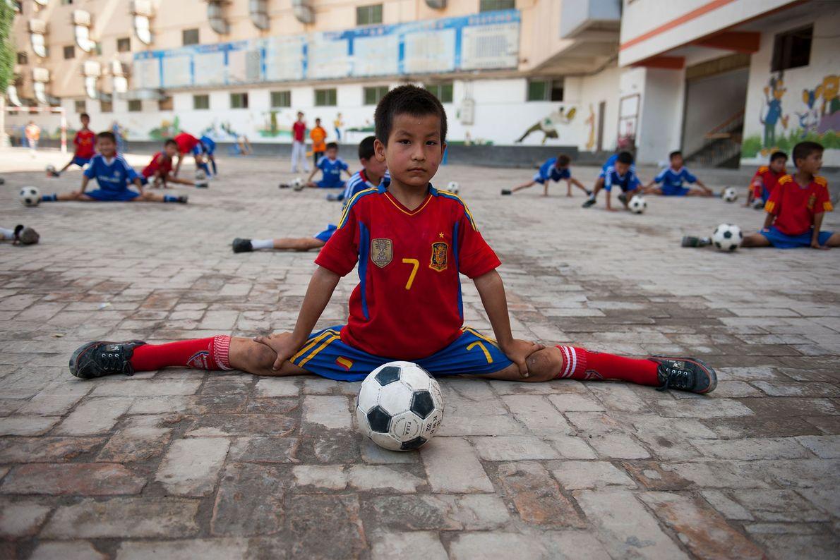 Un jeune joueur de football s'étire avant de jouer dans la province de Xinjiang, en Chine, ...