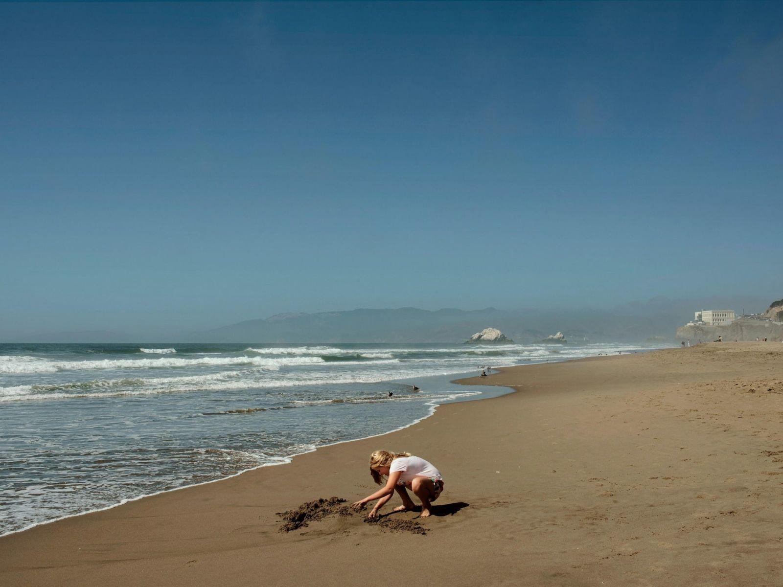 Blonde girl playing with sand on Ocean Beach, San Francisco, California, USA. Sep 2019