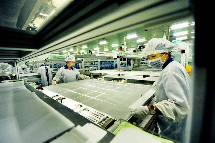 Les ouvriers d'un établissement Jinko Solar situé à Shangrao fabriquent des cellules solaires.