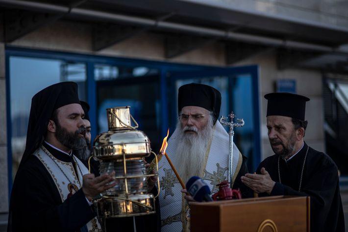 Archimandrite Damianos porte une lanterne à l'aéroport international d'Athènes allumée du Feu sacré rapporté de Jérusalem ...