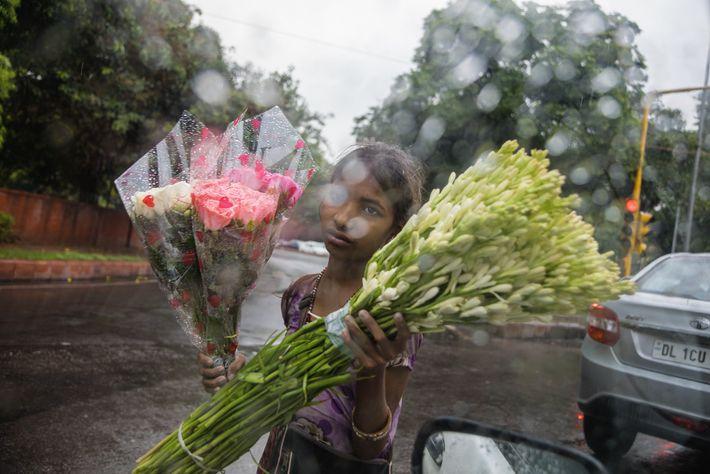 Aarti, petite fille âgée de neuf ans, vend seule des fleurs dans une rue de Delhi, ...