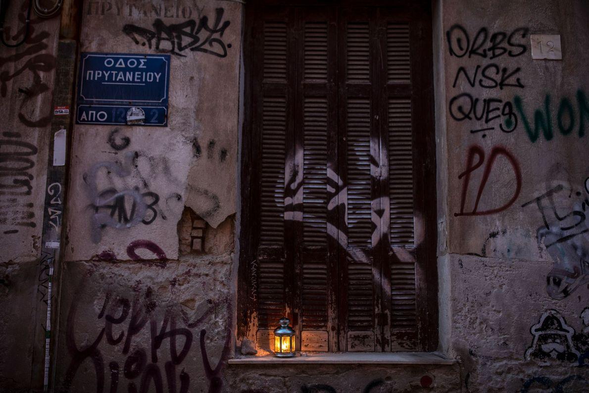 Le Feu sacré illumine une lanterne près de la porte fermée de l'église Metohi Panagiou Tafou ...