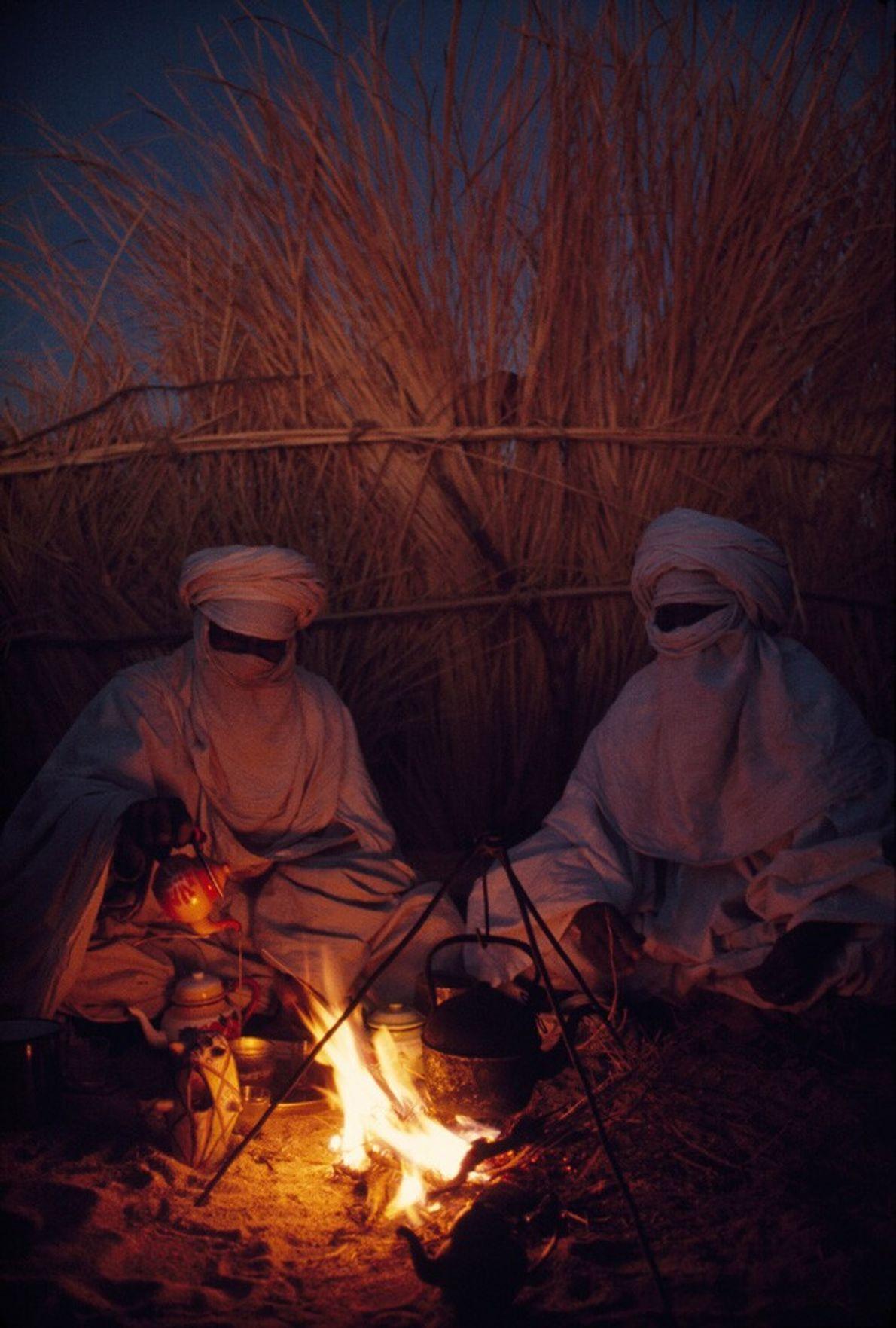Algérie, 1973 : des éleveurs de chèvres du peuple Touareg boivent leur thé au camp Hassi Izernene ...