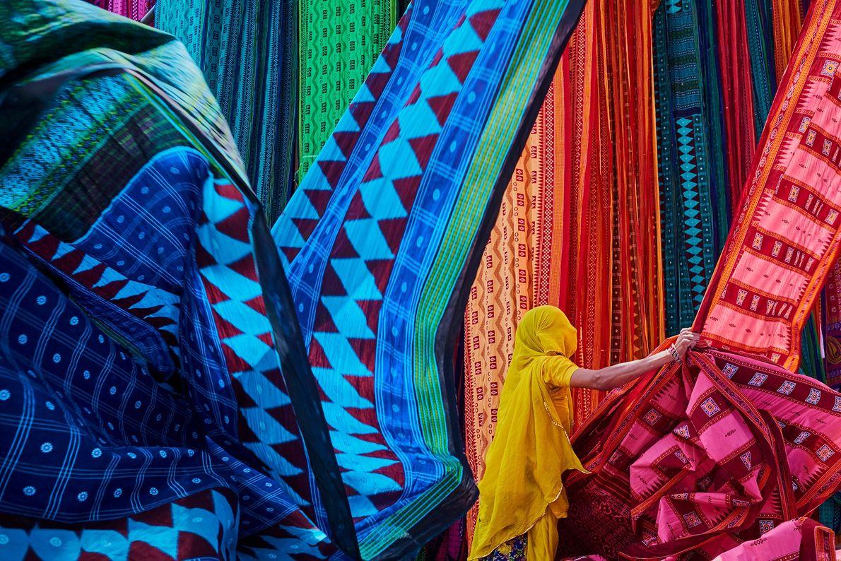 Dans une usine de saris au Rajasthan, une ouvrière suspend des textiles tout juste teints pour les ...
