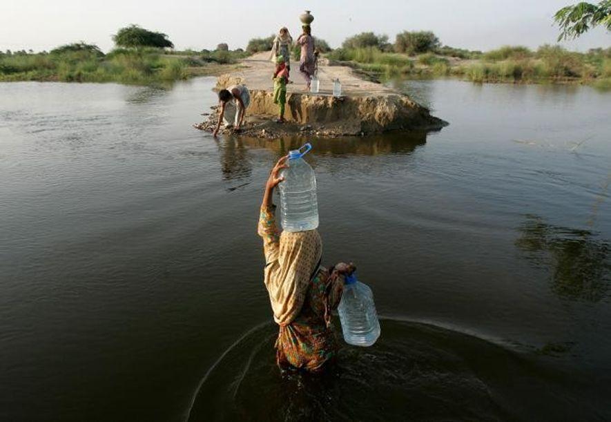 En août 2010, une femme pakistanaise transporte de l'eau potable sur une route de Baseera, endommagée ...
