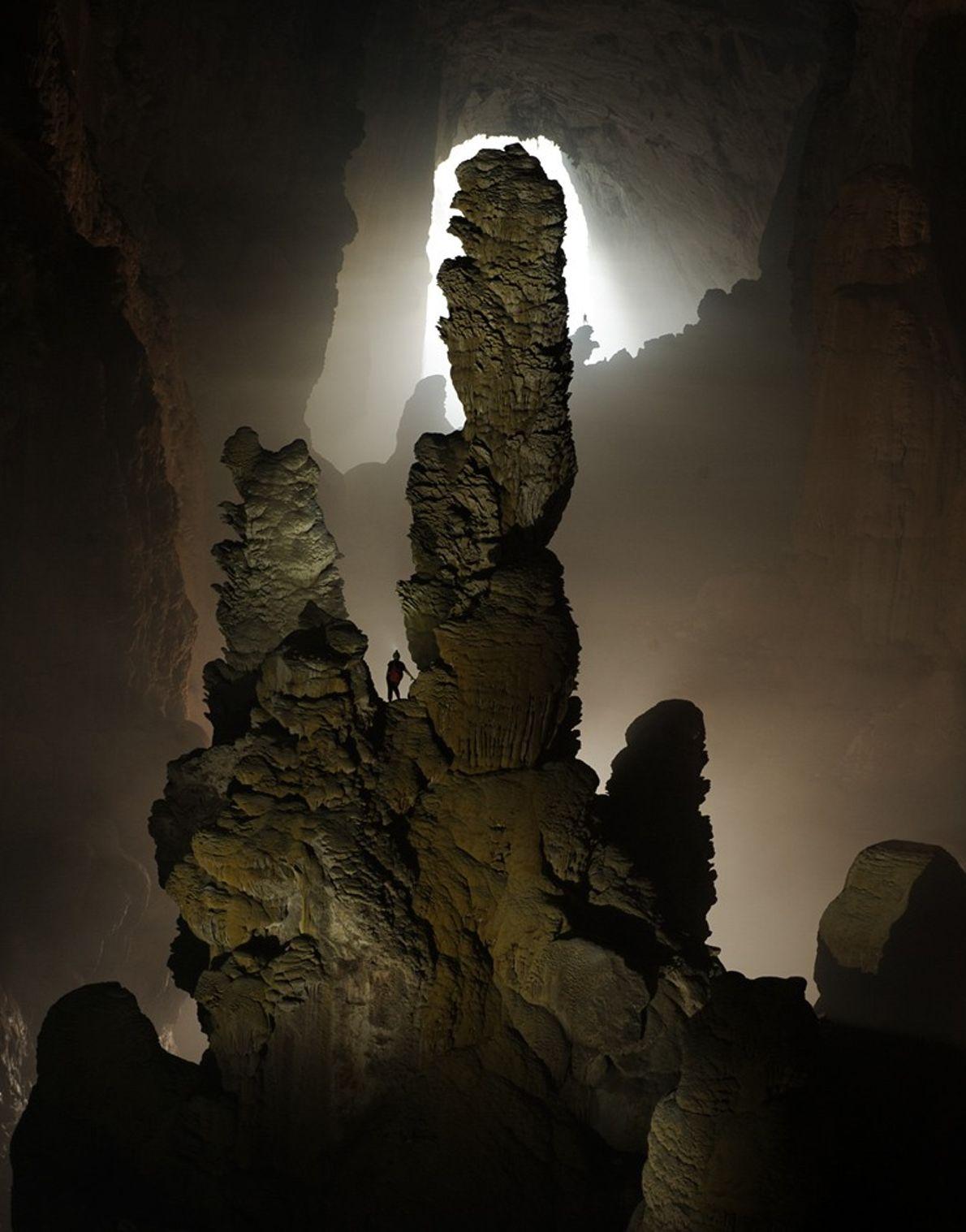 Un spéléologue observe de près la stalagmite connue sous le nom de Hand of Dog (main ...