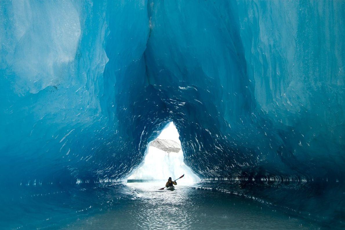 Un kayakiste de mer traverse une grotte de glacier taillée dans les icebergs géants de Resurrection ...