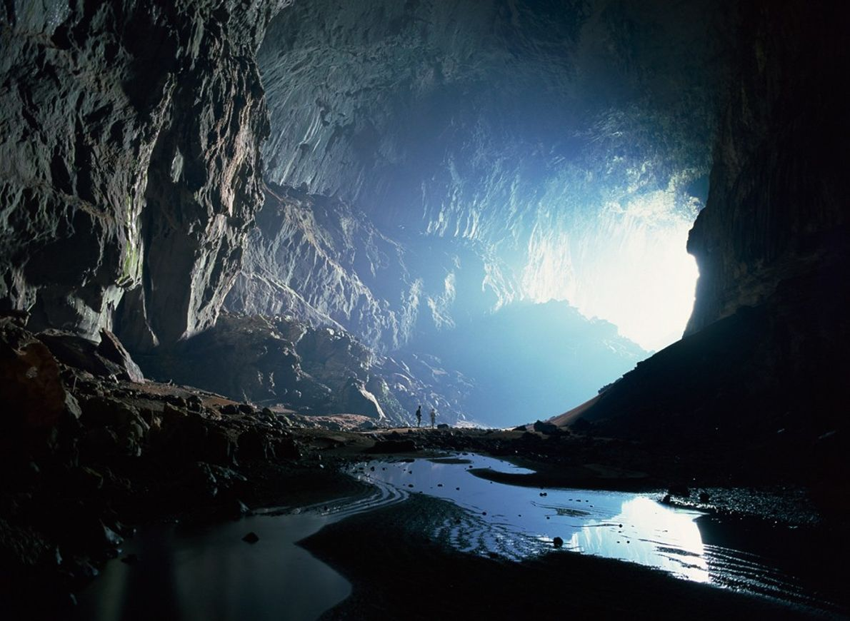 Deux minuscules silhouettes observent l'entrée de la caverne du Cerf (Deer Cave) dans le parc national ...