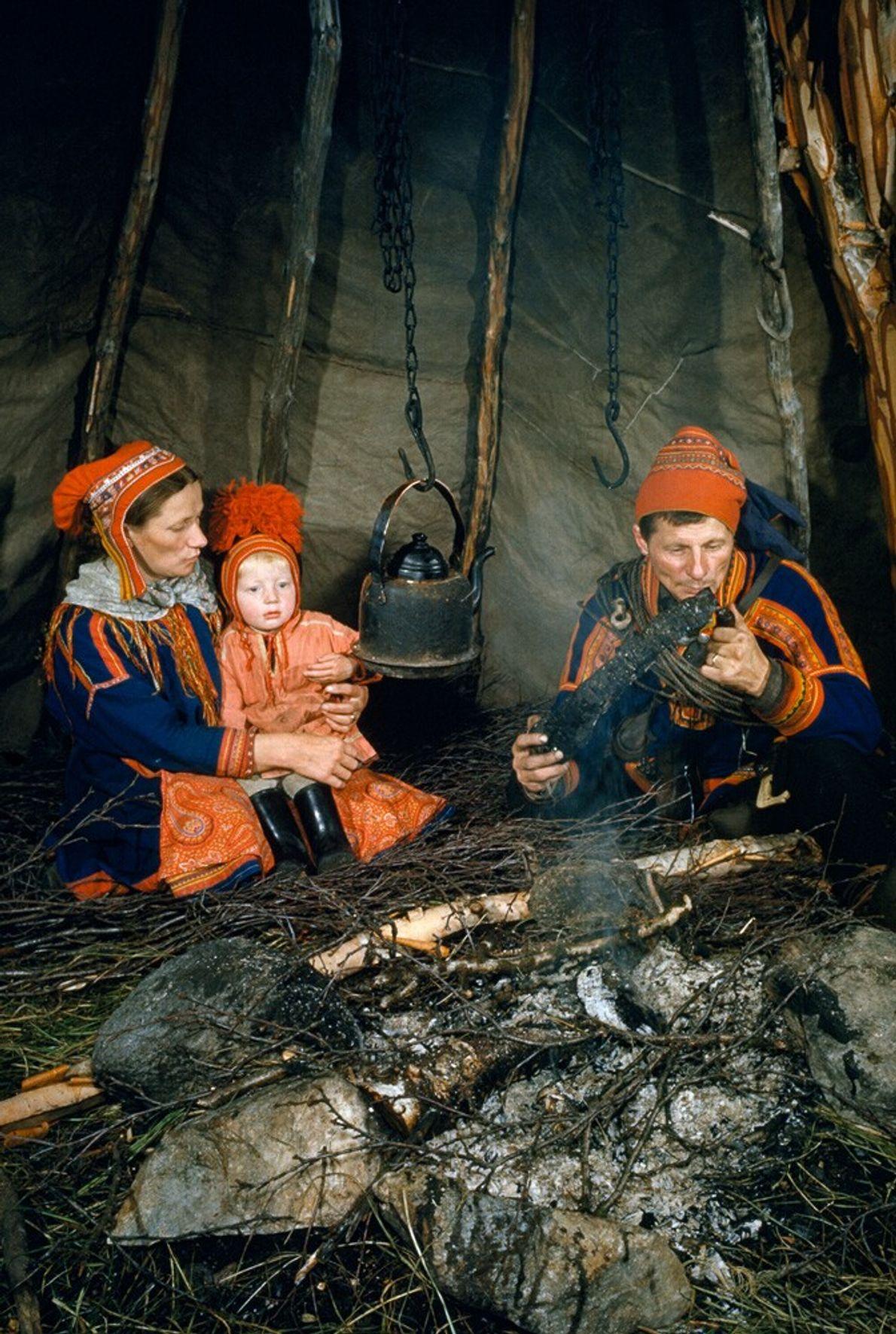 Finlande, 1954 : une famille Sami est assise autour du feu, à l'abri dans un tipi en ...