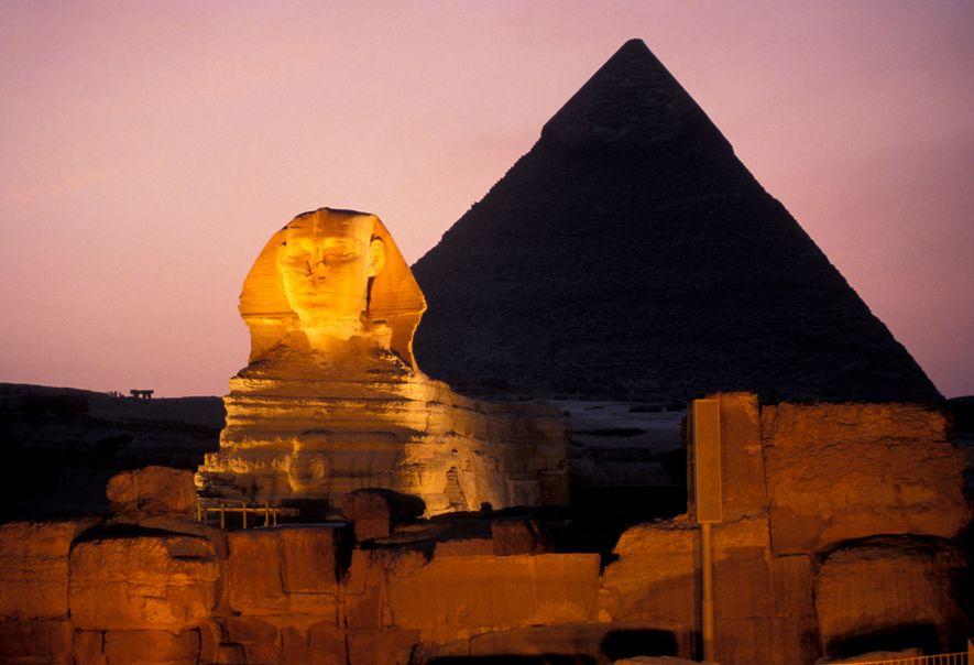 Les pyramides et un sphinx protecteur photographiés la nuit, à Gizeh, en Égypte.