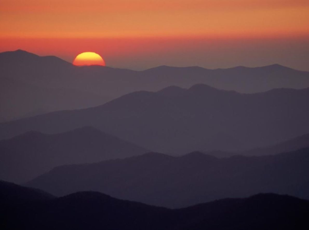 Le soleil se couche sur les sommets du parc, qui s'alignent parfaitement. Seize sommets dans le ...