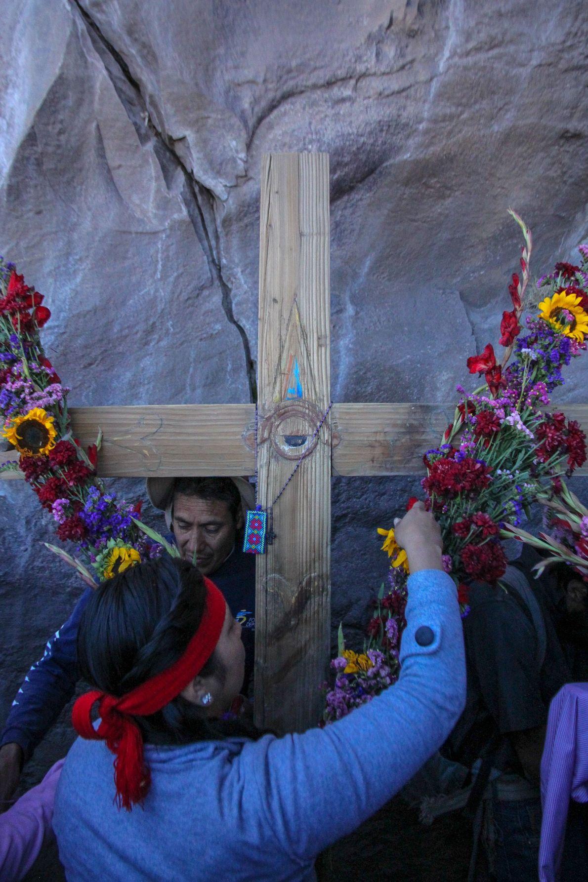 Les préparatifs se terminent, la cérémonie est proche. Ici une fidèle habille une croix de fleurs ...