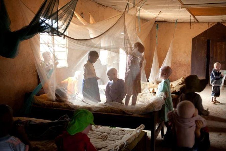 Dans un dortoir bondé du Kabanga Protectorate Center, des enfants albinos jouent calmement derrière les moustiquaires. …