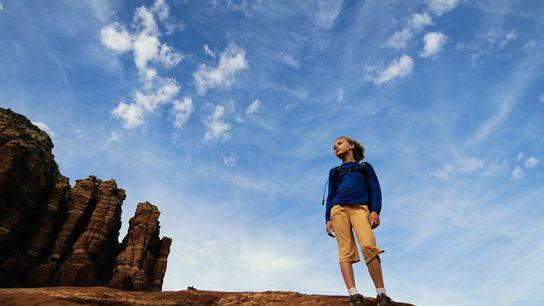 Une jeune fille admire un paysage désertique.