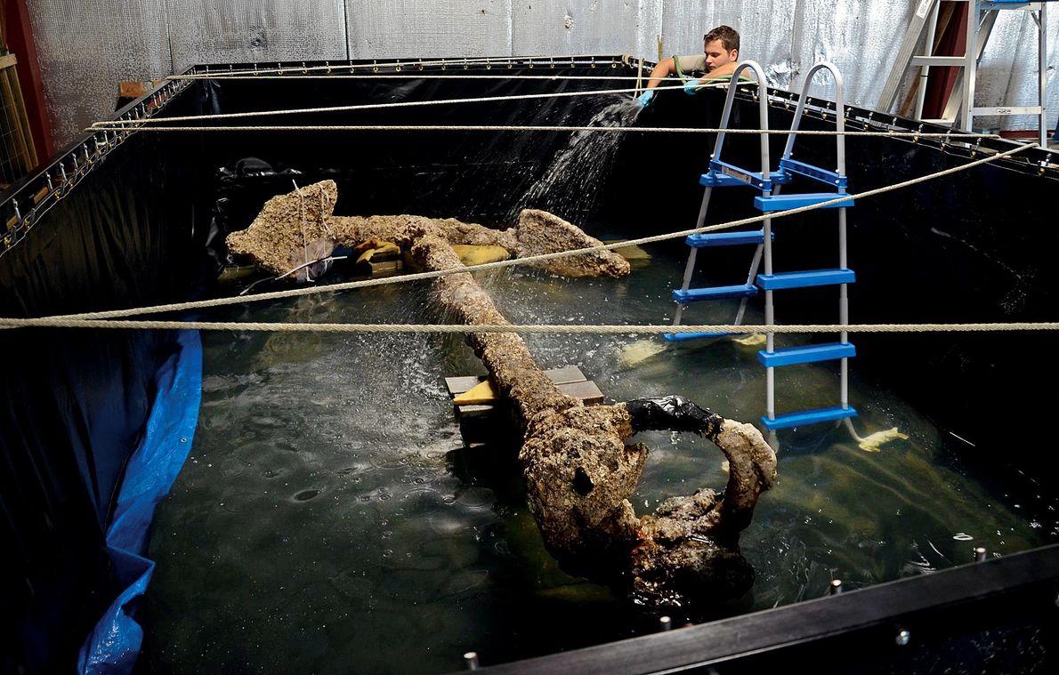 Un conservateur nettoie une ancre retrouvée sur l'épave du Queen Anne's Revenge avec de l'eau pour ...