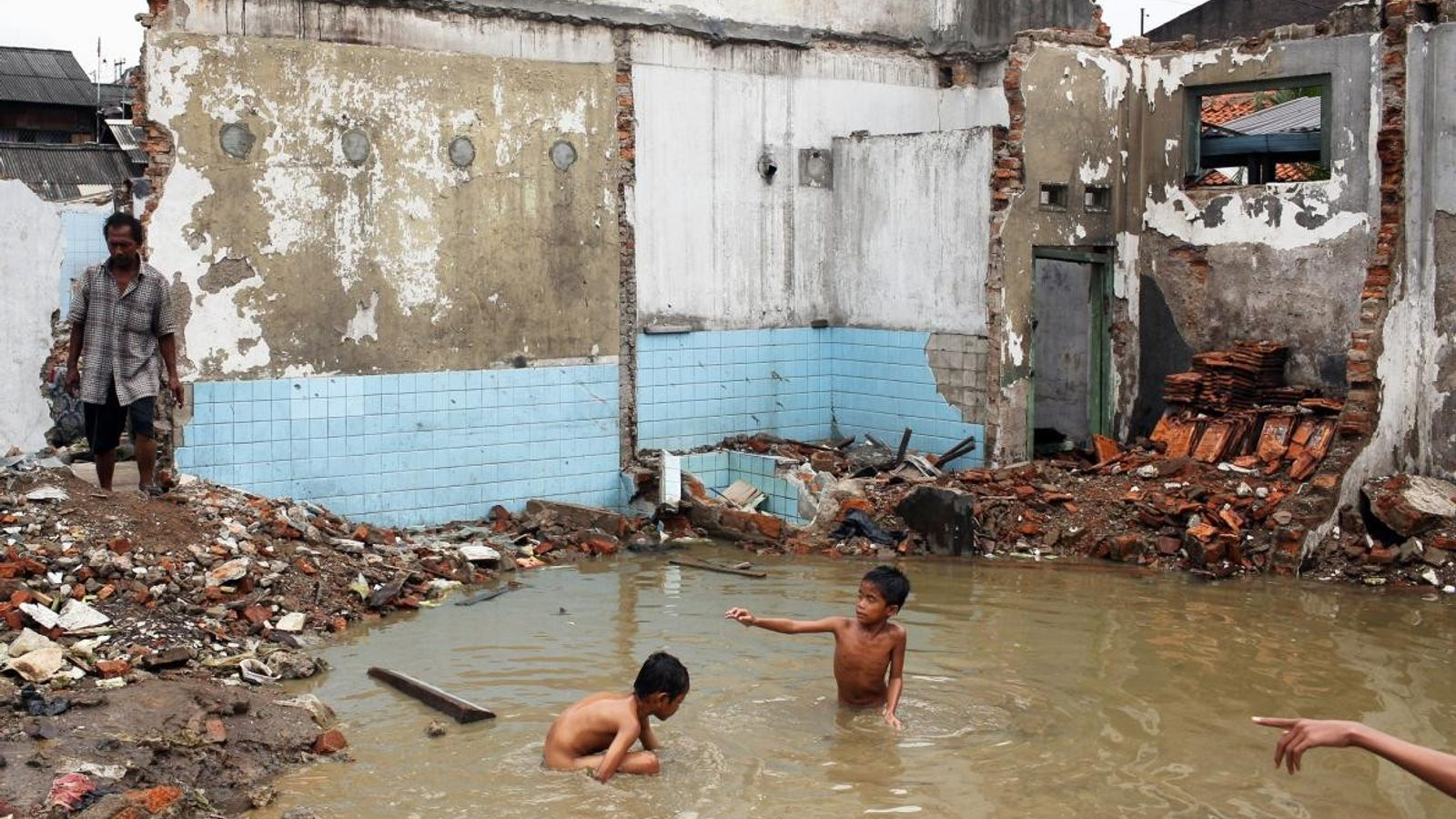 Des enfants jouent dans les ruines inondées d'un immeuble abandonné après la montée des eaux en ...