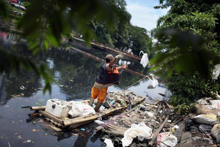 Un employé municipal retire les déchets d'un canal de drainage dans le centre de Jakarta en ...