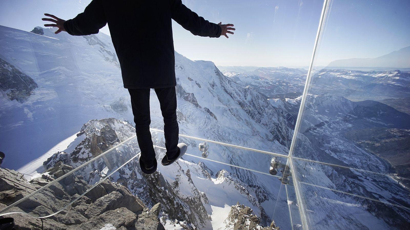 Photo d'un journaliste dans une boîte de verre au-dessus des Alpes