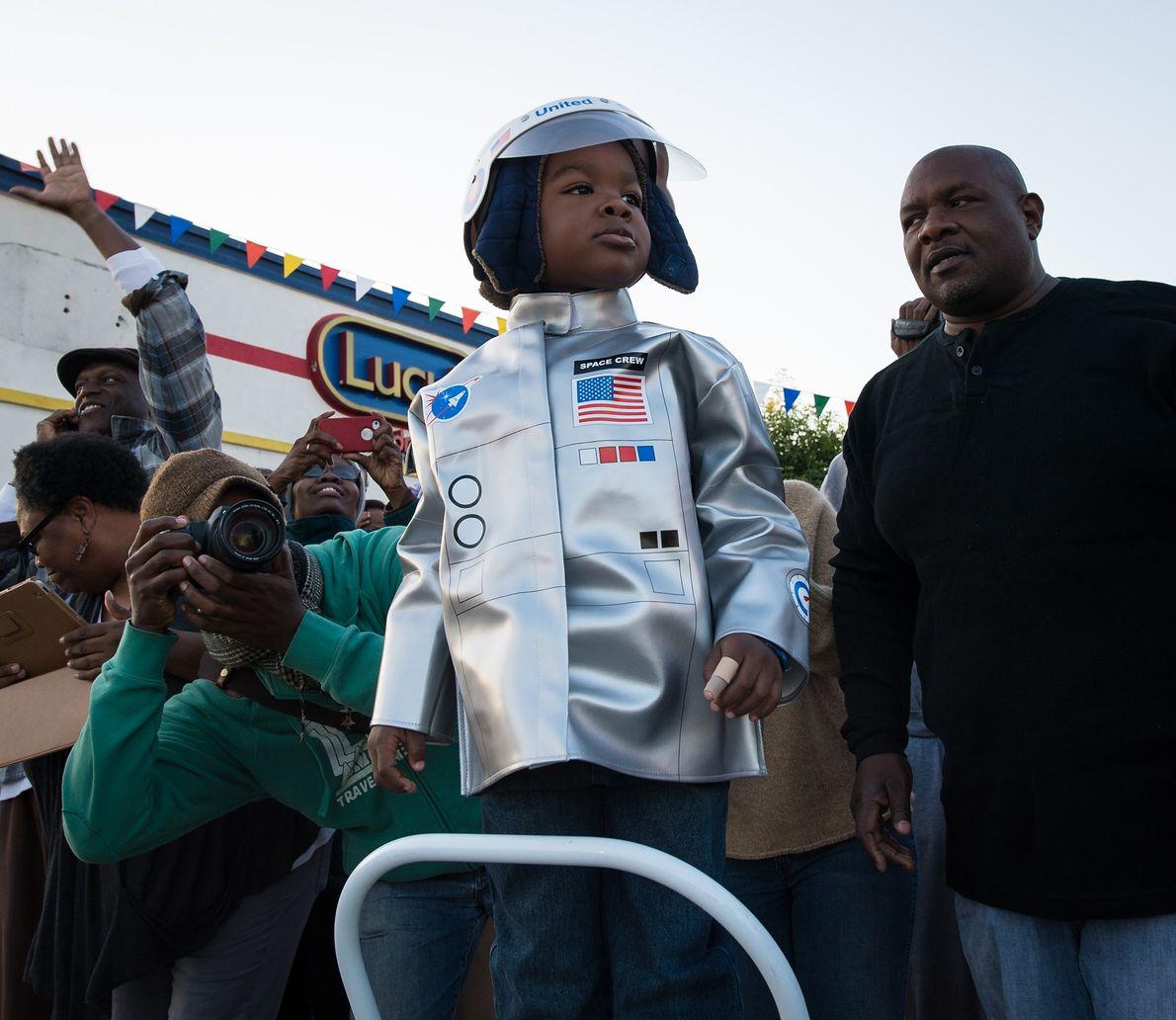 Déguisé en astronaute, un jeune spectateur regarde passer la navette spatiale Endeavour alors qu'elle se dirige ...