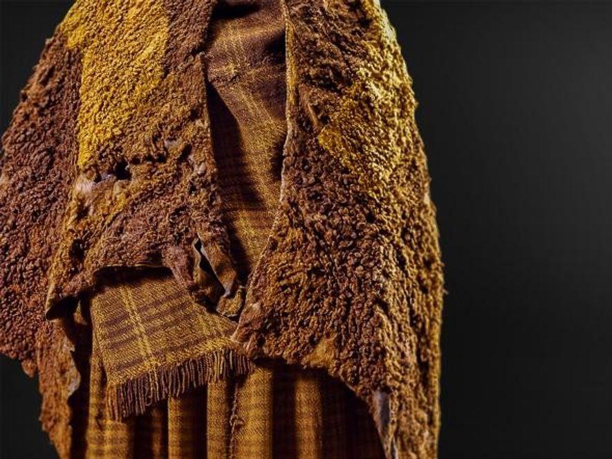 L'analyse de la cape en peau de bête, du foulard et de la jupe en laine ...