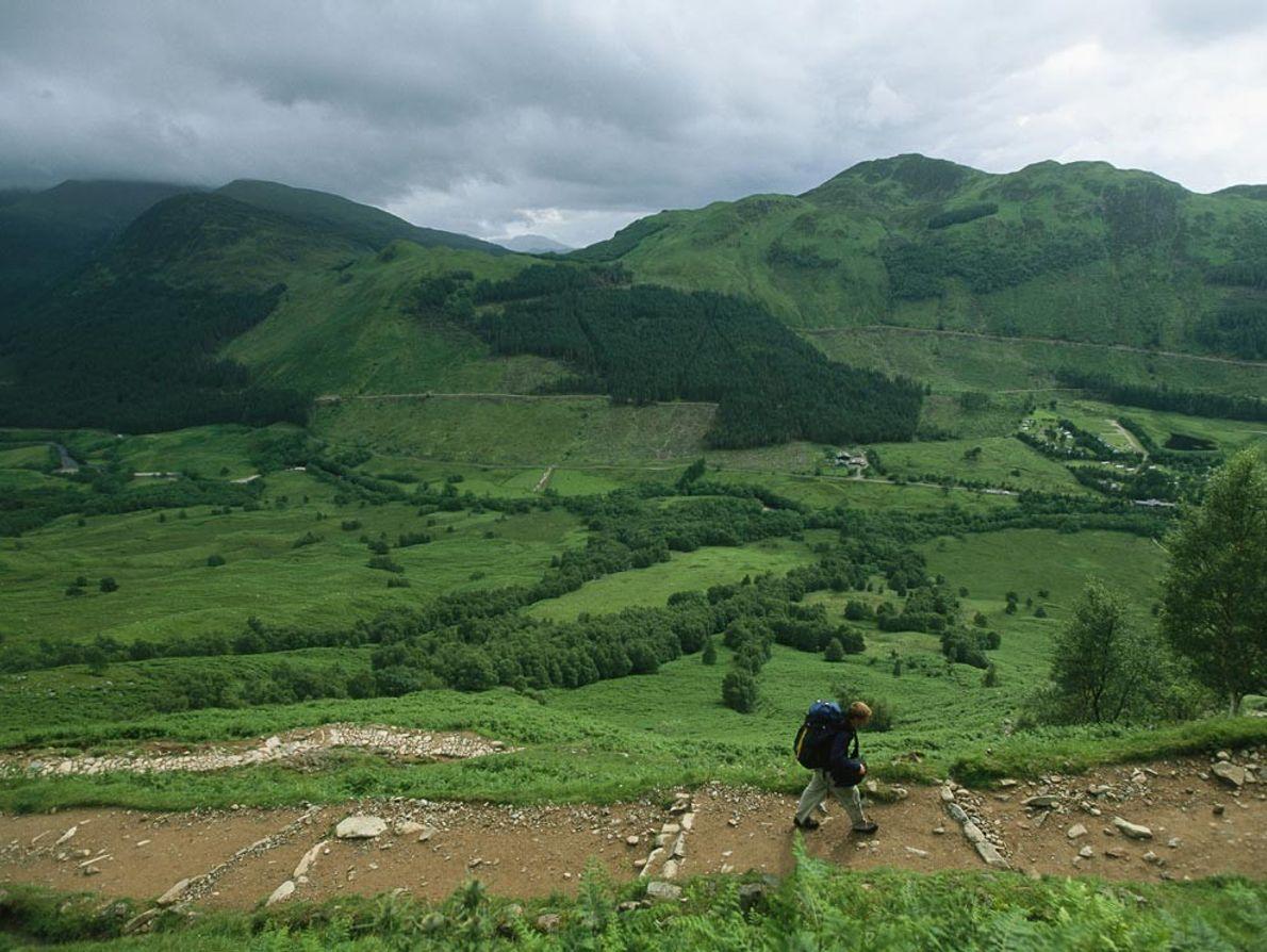 En Écosse, un randonneur solitaire s'aventure sur le sentier qui mène au Ben Nevis sous un ...