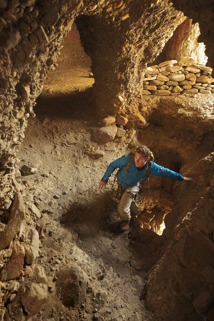 Ted Hesser pénètre dans le labyrinthe de pièces jadis habitées d'une grotte pillée.