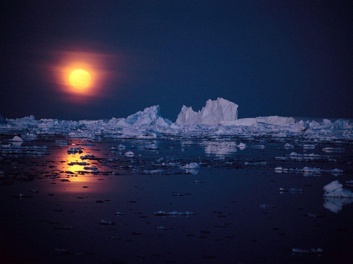Des nuages fins donnent un éclat rougeoyant à la pleine lune au-dessus de l'océan parsemé d'icebergs ...