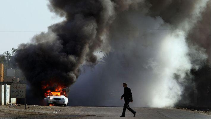 Un homme marche dans un décor de flammes, en Syrie.