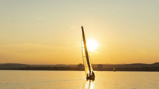 Un voilier solitaire vogue sur les eaux du lac Balaton, plus grand lac d'Europe centrale où ...