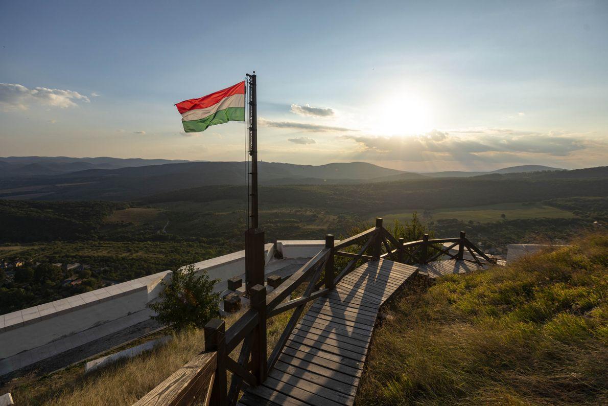 Au coucher du soleil, le drapeau hongrois flotte au-dessus d'un sentier menant au château de Füzér. ...