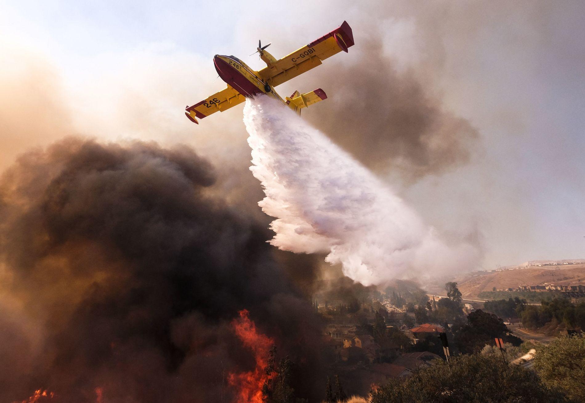 Un bombardier d'eau largue sa cargaison sur un incendie, près de la ville de Simi Valley, ...